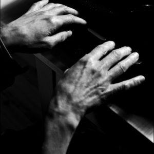 Nainen kirjoittaa vanhalla kirjoituskoneella, vain kädet näkyvät.