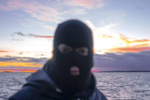 Kuvassa on naamiopipoon pukeutunut musta hahmo, taustalla on auringonnousu.