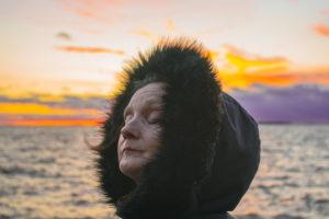 Pääosan esittäjä Anneli Iltanen kuvattuna auringonlaskuavasten. Annelilla on paksu karvakauluksin huppu päässään.