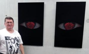Tero Kokko työnsä Ruusun katse edessä. Ruusun katse koostuu kahdesta silmän kuvasta. Silmän keskellä on ruusu.